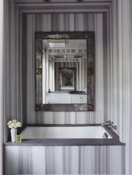 6 gray white striped marble bathroom mirror hung behind bathtub surrounded by marble atticmagdotcom